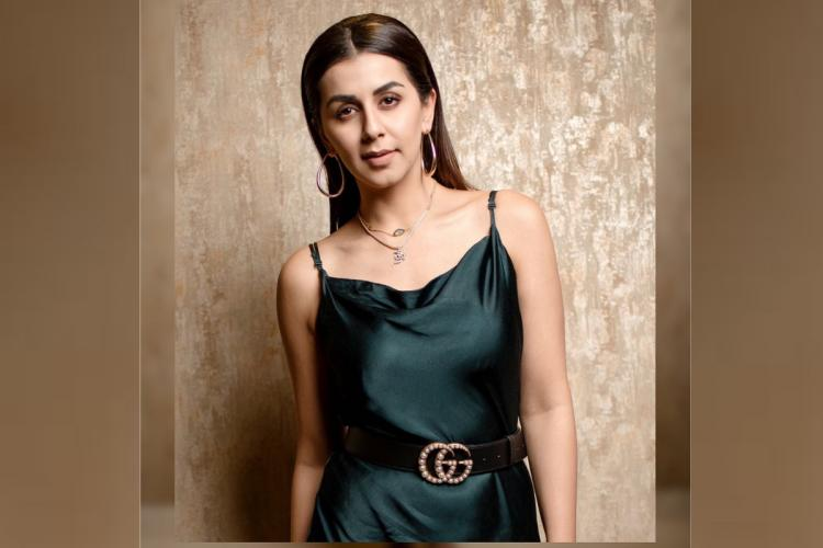 Actor Nikki Galrani looking straight at the camera with a slight smile wearing a black silk spaghetti dress with a stone-studded belt