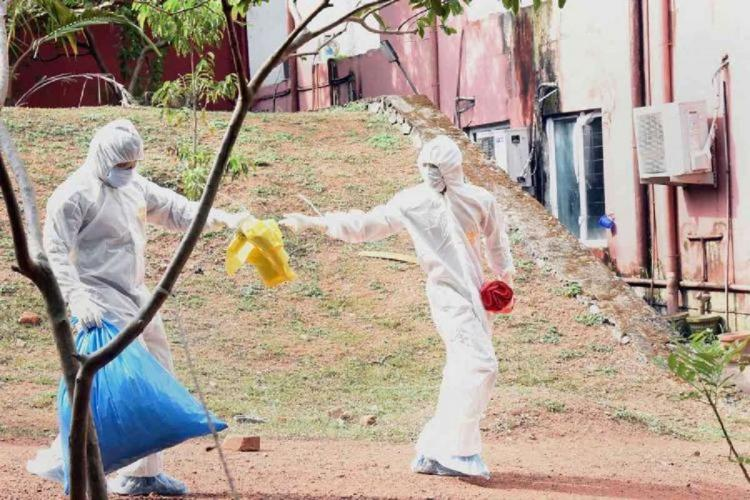 Two people in white PPE kits pass yellow covers between each other, one is holding a blue cover as well
