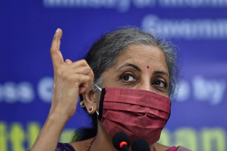 Close up of Finance Minister Nirmala Sitharaman wearing a pink mask and pointing a finger upwards during a press conference