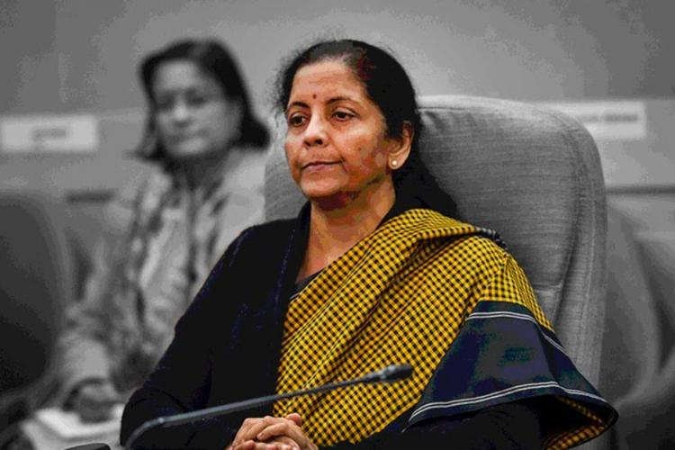 Nirmala Sitharaman in a mustard saree and black sweater siting on a chair