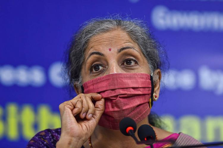 Nirmala Sitharaman wearing a maroon coloured mask speaking into a mic at a press conference in Chennai