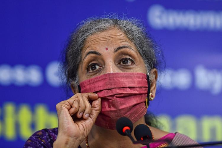 FM nirmala speaking at a press conference closeup shot wearing a pink mask