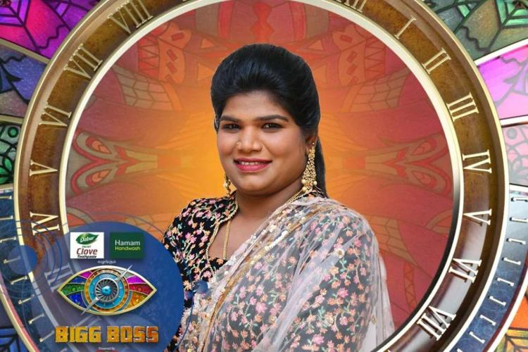 Nisha standing in front of the Bigg Boss logo