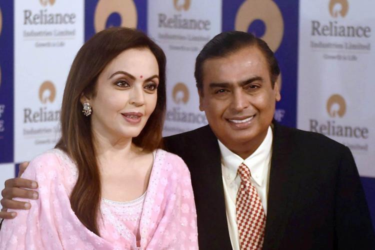 Nita and Mukesh Ambani together Mukesh Ambani wearing a suit is looking straight at the camera and smiling Nita Ambani clad in a pink salwar is looking forward towards the right