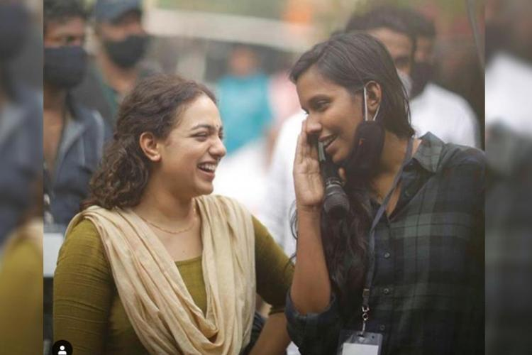 Nithya Menen and Indhu VS laughing during shooting set of the movie Nithya Menen is wearing a simple olive salwar kameez and Indhu is wearing a check pattern shirt
