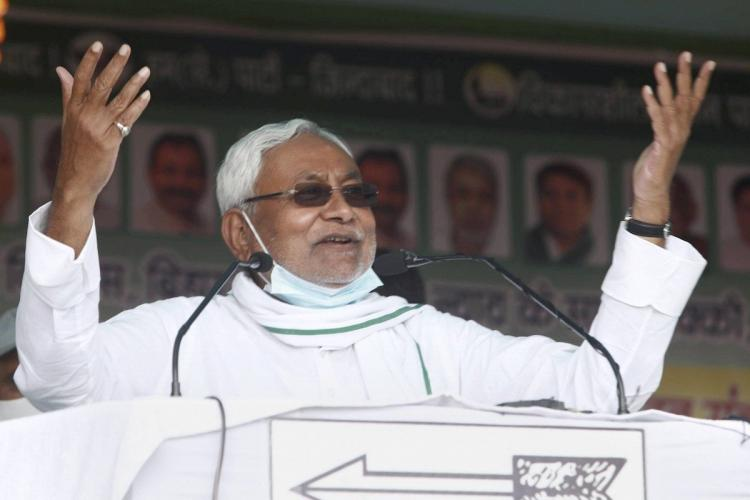 Nitish Kumar gestures to the audience wearing a white shirt and a mask on his chin