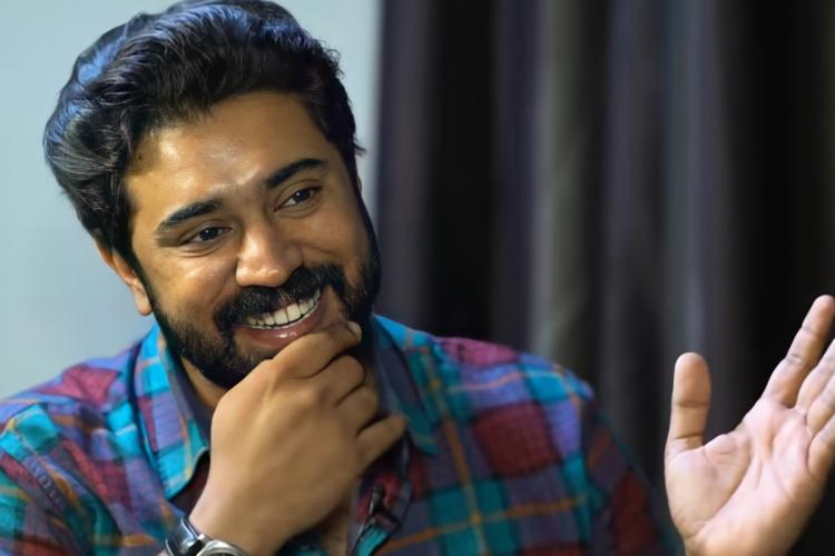 Nivin Pauly wearing a blue and maroon check shirt smiles, he has one hand on his beard and the other is gesturing