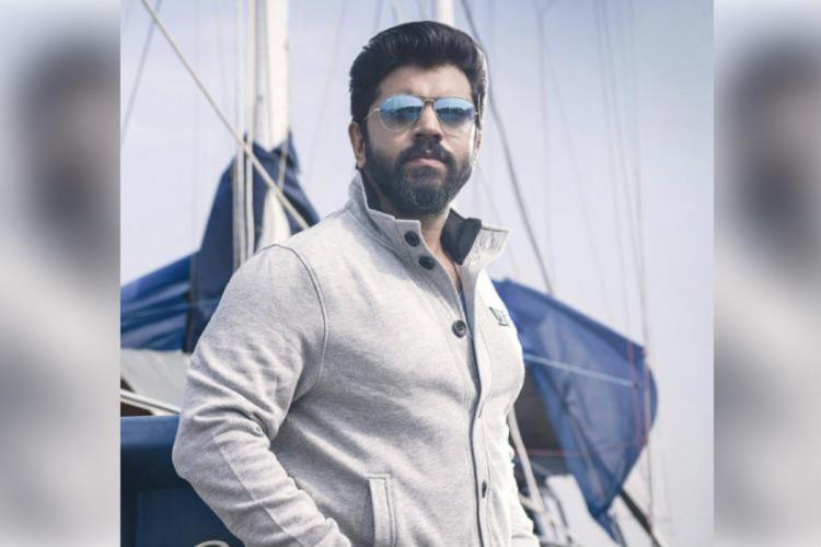 Actor Nivin Pauly is seen wearing a light coloured shirt and shades