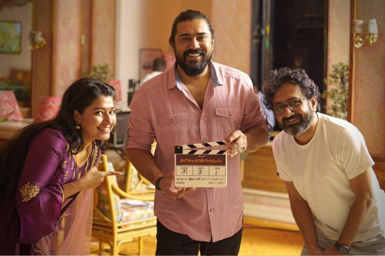 Nivin stands with the clapboard for film shooting in the middle flanked by Grace on the left and Ratheesh on the right