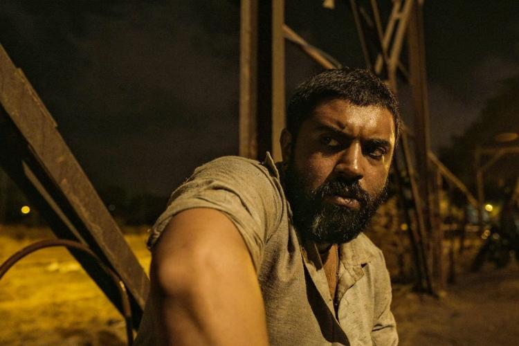 Nivin with closely trimmed hair on his head and a beard looks fierce in the night as he sits wearing his grey kurtha