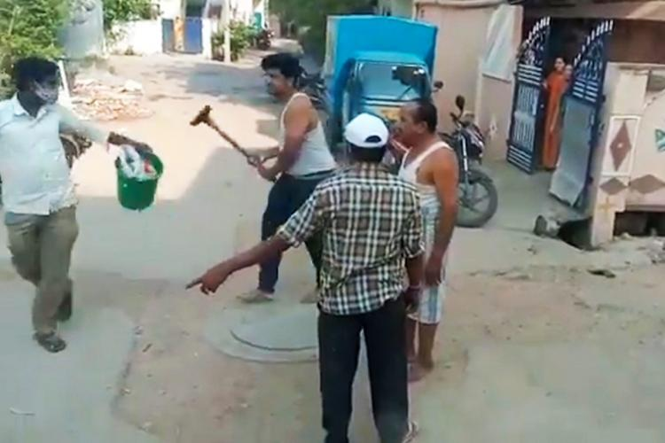 A man about to hit a sanitation worker in Nizamabad