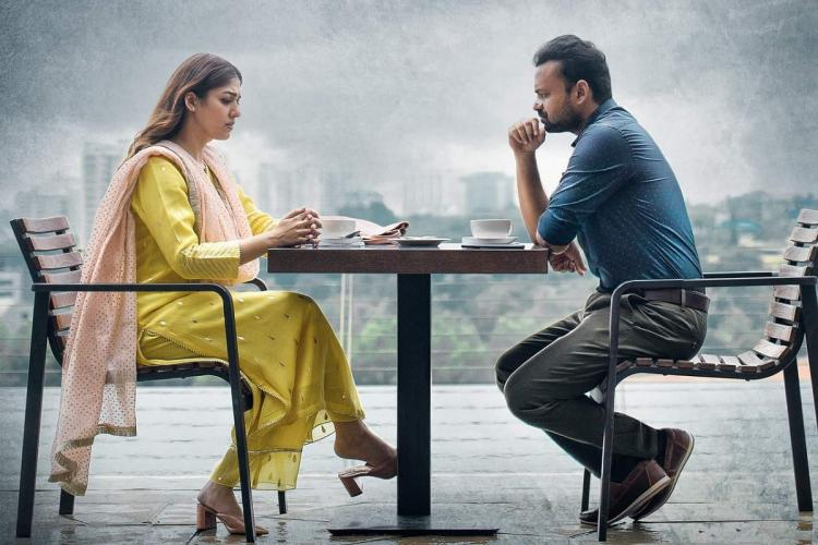 Nayanthara in a yellow salwar sits opposite Kunchacko Boban in a blue shirt across a table and the background is a cloudy grey