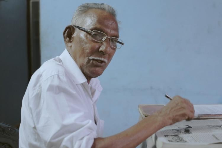 Njattyela Sreedharan wearing a white shirt and specs is sitting in front of papers a pen in his hand