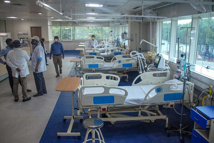 Empty hospital beds with doctors in masks standing nearby