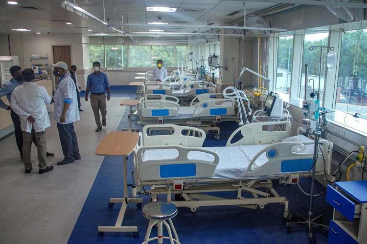 Unoccupied hospital beds at a COVID hospital in Noida with staff members standing nearby in a group