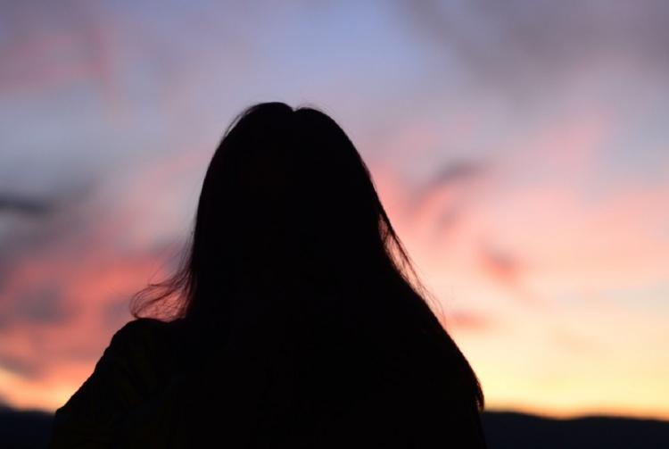 The silhouette of a teenager against the setting sun