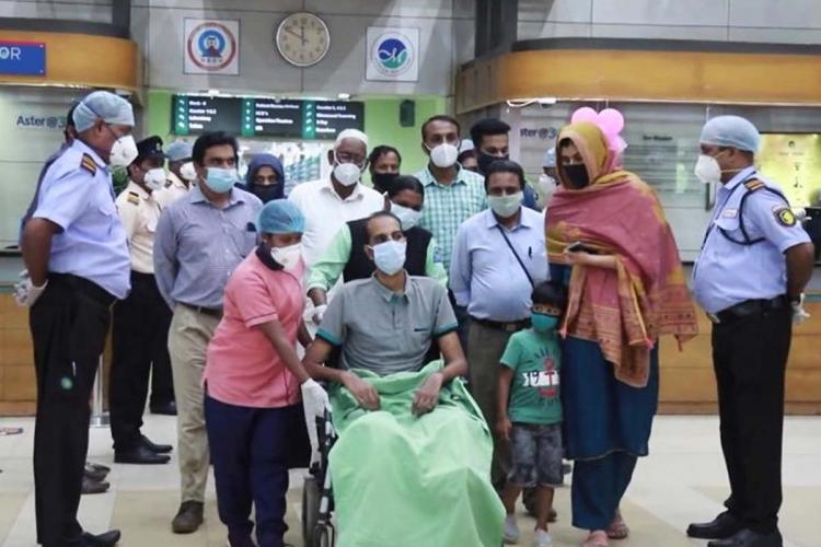Karipur flight crash survivor Noufal sitting in a wheelchair. His wife, son and other hospital staff are seen standing around him.