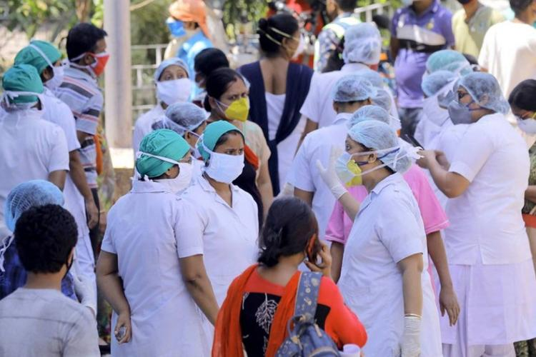 A number of nurses in white uniform and masks stand around and talk