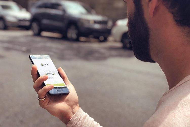 Man using a phone with Ola app shown on mobile screen