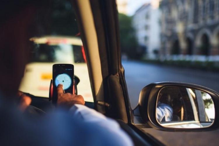 Representative image of a cab driver checking his mobile phone while seated in the cab
