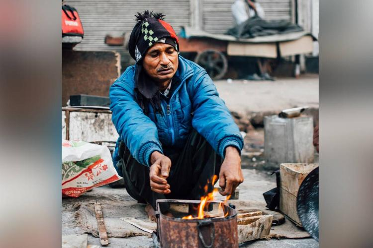 A man in a blue jacket and black muffler tied around his head warming himself in front of a small fire