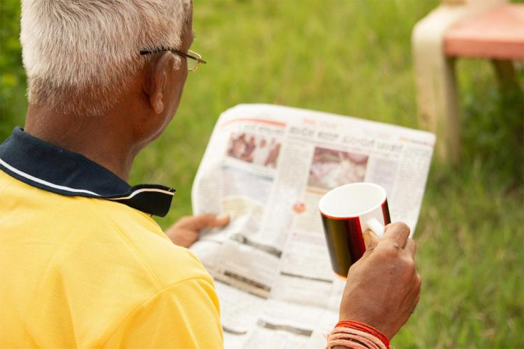 A senior citizens reading a newspaper and holding a mug The man is seen wearing a yellow t-shirt