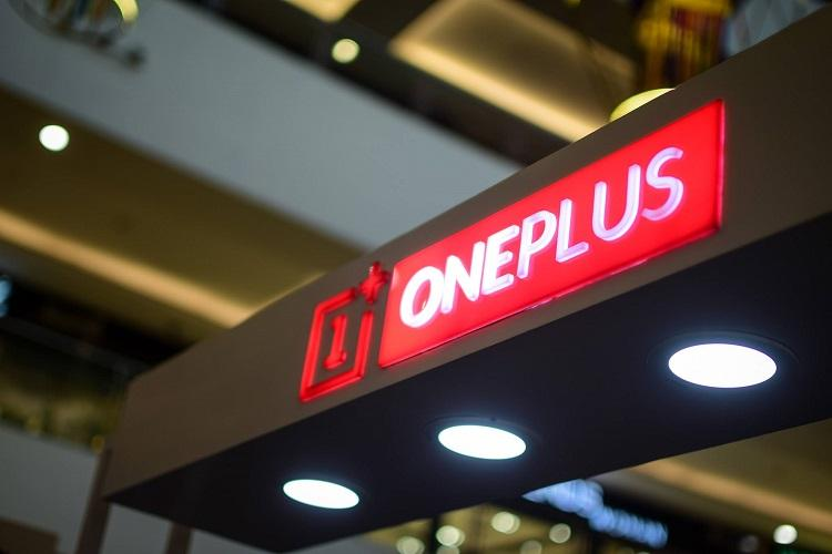 The branding of OnePlus in red on a black background hanging in front of a store