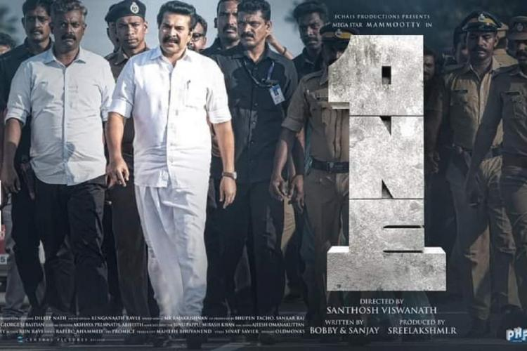 Mammootty in white shirt and mundu walks with a few men some policemen among them next to a big block of digit 1