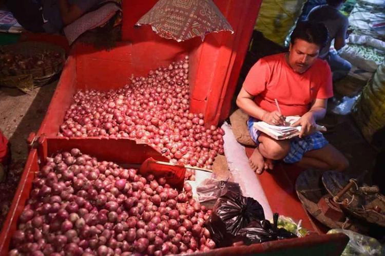 Man sitting beside heap of onions