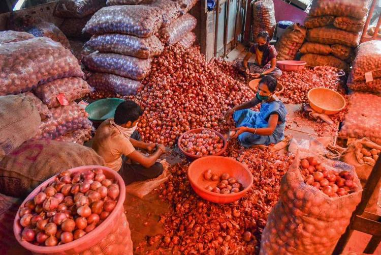 Workers sort onions at a vegetable market in Thane