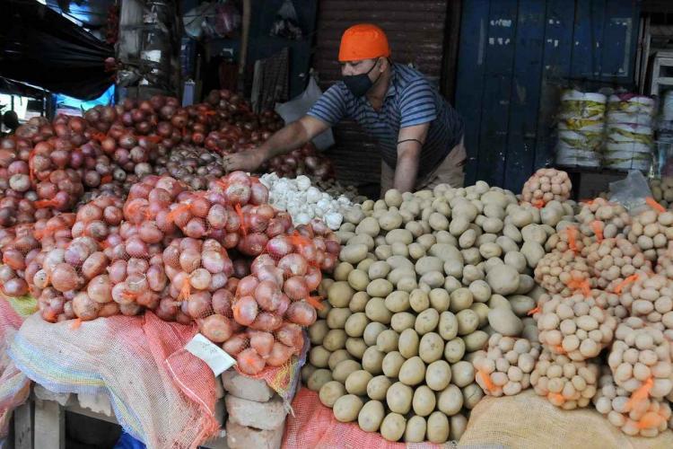 A vendor sorts onions as prices increase at Lake Market in Kolkata
