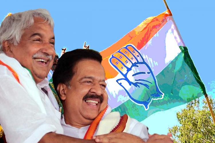 Oommen Chandy and Ramesh Chennithala hug each other in the picture The Congress party flag is seen in the background