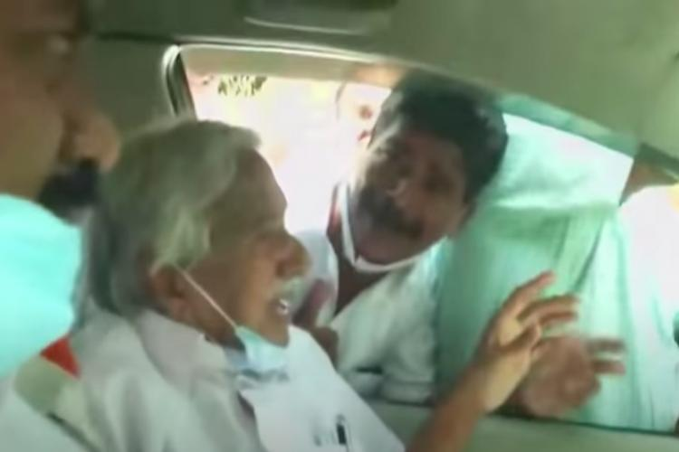 Oommen chandy sitting inside his car while protesters throng outside