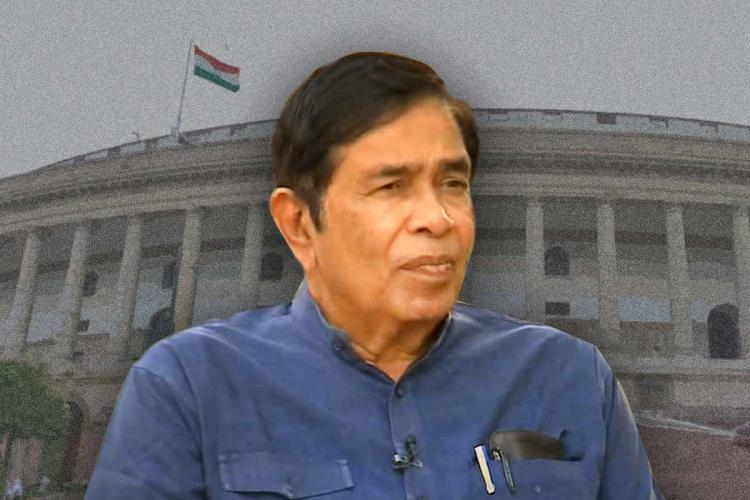 Oscar Fernandes in a blue shirt, against the backdrop of the Parliament building in New Delhi