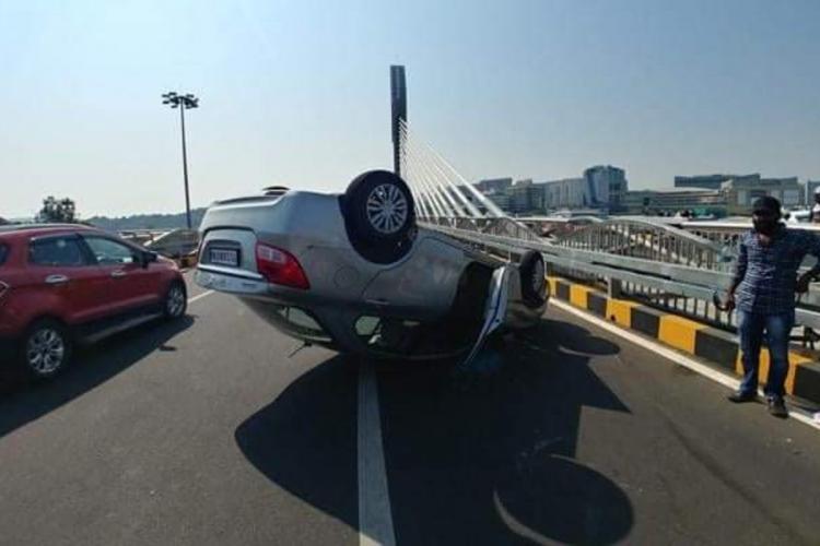 Overturned car on Durgam Cheuruvu cable bridge as a bystander looks on