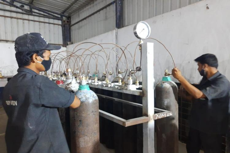 Two workers at an Oxygen refilling plant in Hyderabad