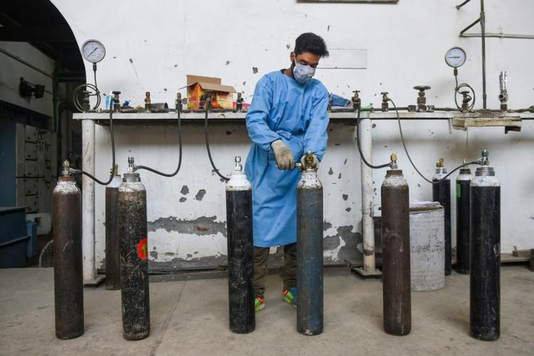 A worker refills oxygen containers used for COVID-19 patients inside a medical oxygen gas plant