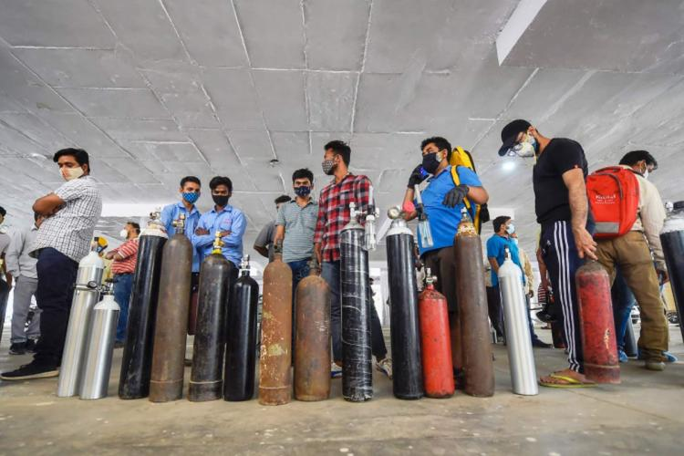 People standing in queue with oxygen cylinders