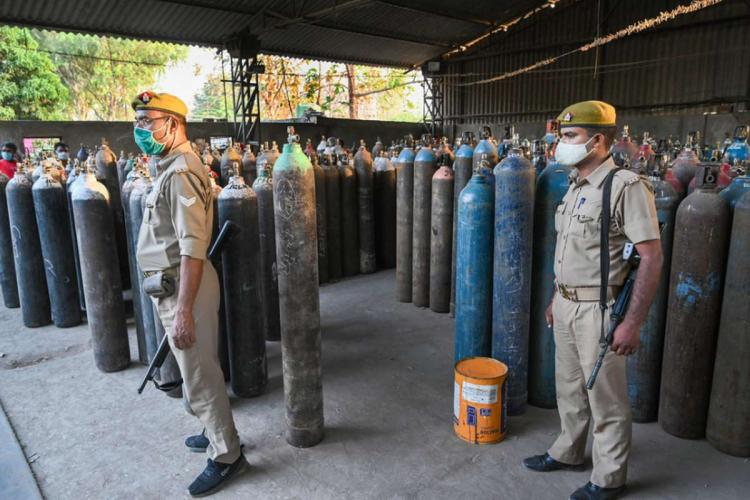 Policemen keep vigil as family members of COVID-19 patients wait to fill their empty cylinders with medical oxygen outside an oxygen filling center as demand for the gas rises due to spike in coronavirus cases in Prayagraj
