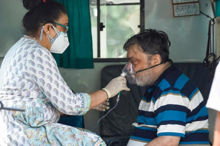 A COVID-19 patient taking in oxygen through an oxygen mask with a woman wearing a n95 mask sitting in front of him