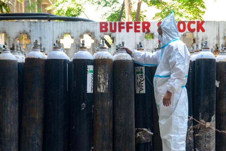A health worker standing in front of a line of oxygen cylinders arranged outside a hospital