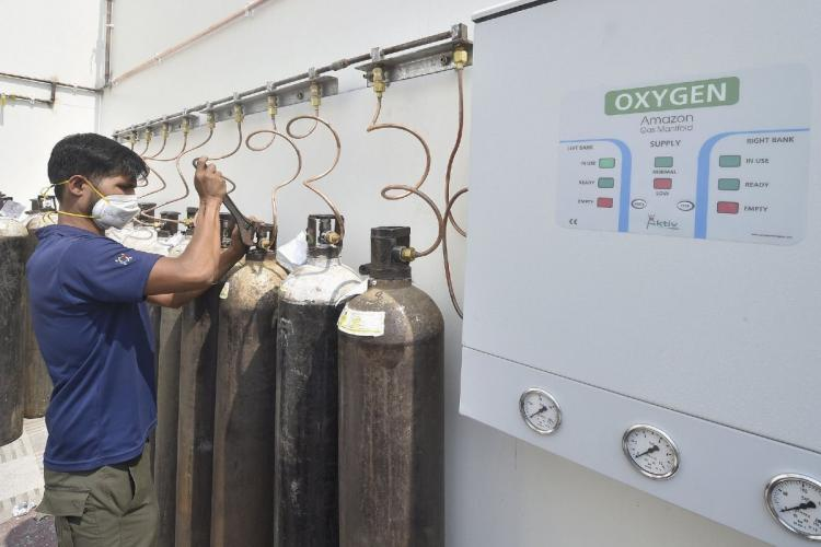 A man fixing an oxygen cylinder he is wearing a mask