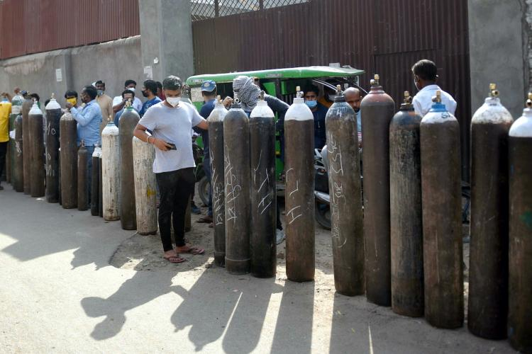 People wait in line amid a row of oxygen cylinders