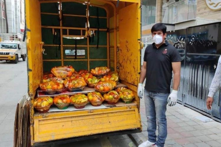 Corporator Imran Pasha stands next to a van full of goods for distribution during covid19