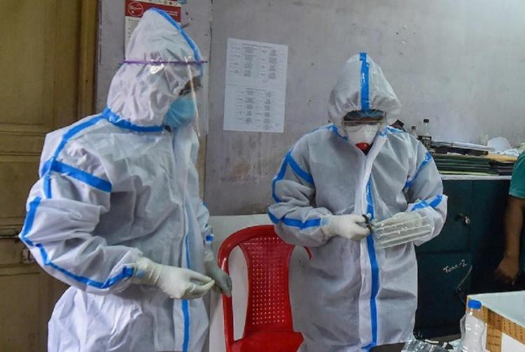 Two doctors dressed in PPE suits analysing samples