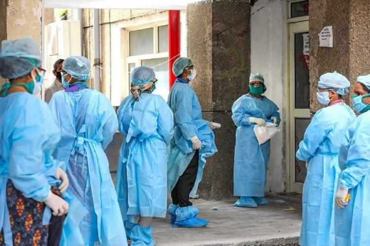 Doctors wearing blue PPE kit in a hospital building outside a room