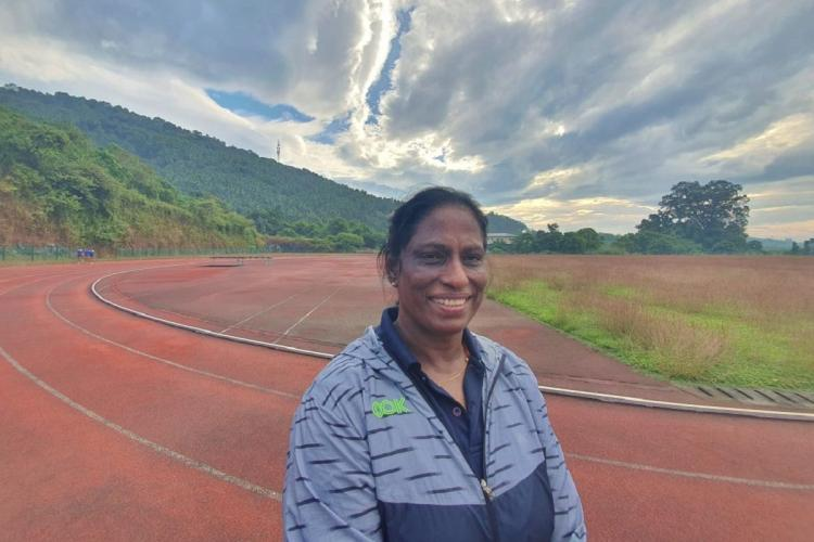 PT Usha in a blue top smiles as in the background you see a racing ground greenery and a cloudy sky