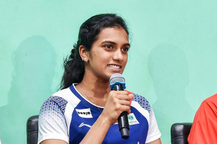 Indian badminton player PV Sindhu at a press conference holding a mic and smiling