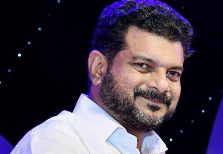 A close up shot of Nilambur MLA PV Anwar He is wearing a white shirt and smiling at the camera