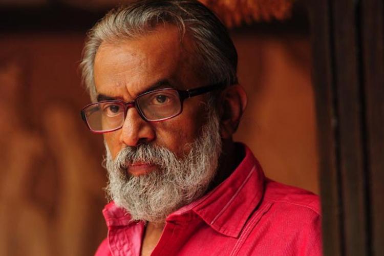 Malayalam actor P Balachandran wearing a red shirt and glasses